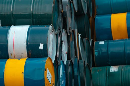 Old chemical barrels stack. Blue, green, and yellow chemical drum. Steel tank of flammable liquid. Hazard chemical barrel. Industrial waste. Empty chemical barrels at the factory warehouse.