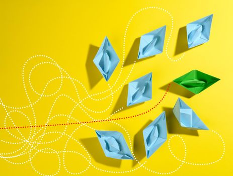 a group of blue paper boats and one green with paths on a yellow background. The concept of a strong leader with extraordinary thinking