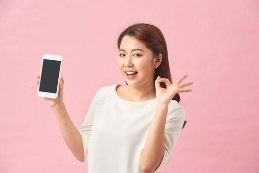 Asian female making finger symbol on smartphone