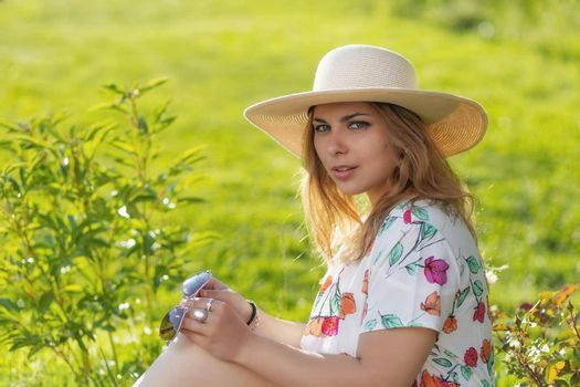 Portrait of attractive  young woman in straw hat posing outdoors.