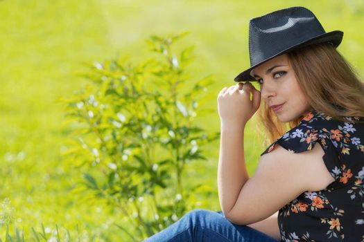 Portrait of attractive beautiful young woman in black hat.