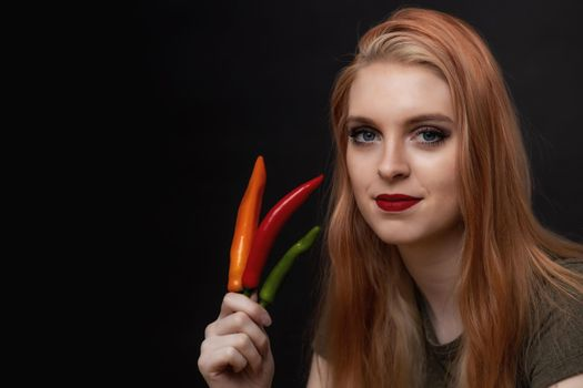 Attractive young woman is posing with chili peppers