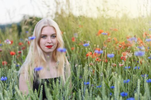 Blonde young woman is posing in a cereal field with poppies and cornflowers.