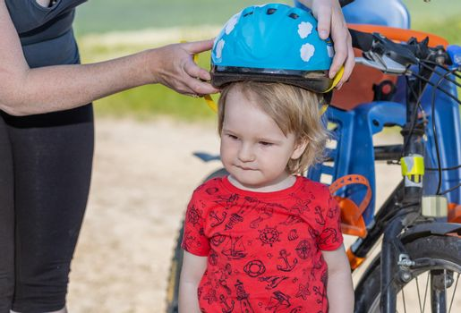 Mother puts on the  head of little boy safety helmet