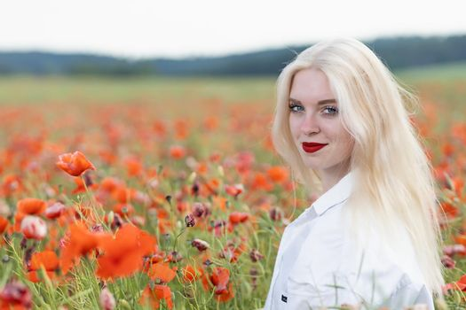 Portrait of blonde young woman posing in red poppy field.