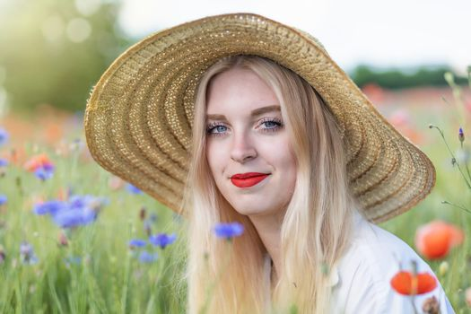 Portrait of beautiful  young woman in straw hat is posing  outdoors