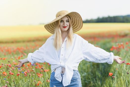 Attractive young woman is standing with her arms outstretched in a field of red poppies.