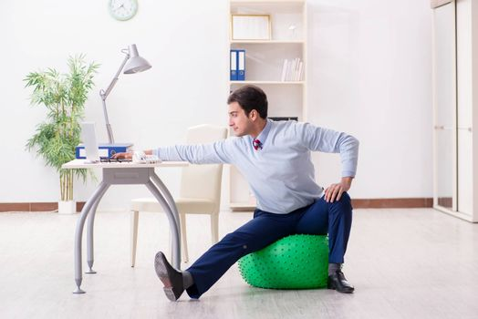 Employee exercising with swiss ball during lunch break
