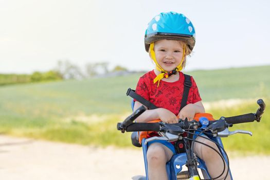 Little boy with safety helmet is sitting in bicycle seat.