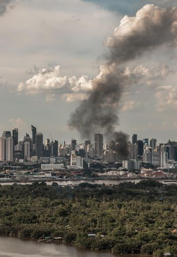 Plume of smoke clouds from burnt building on fire at some area in the city.