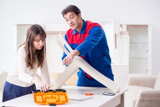 Contractor repairman assembling furniture under woman supervisio