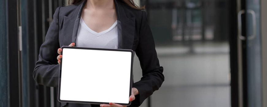 Close-up shot on blank tablet computer showing businesswoman with two hands in a conference room