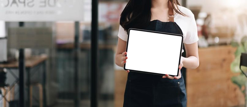 Close up on blank tablet computer that barista show and holding with two hand in front of coffee shop counter bar,Mock up space for display of menu or design.