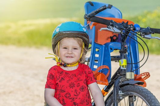 Little boy with safety helmet is posing next to the bicycle.