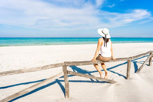 Young woman on vacation alone admires the crystal clear tropical sea sitting on a wooden fence on a white sand beach under blue sky. Pensive girl with large white hat enjoying summer travel