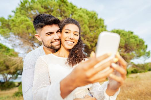 Young beautiful multiracial couple in love taking selfie in nature enjoying vacation moments sharing photos on social networks. New normal technology addiction due to wi-fi internet mobile connections