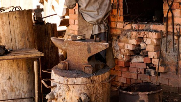 A blacksmith in an authentic workshop. Blacksmithing in the village