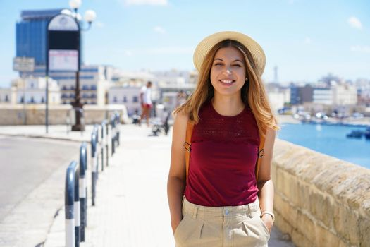 Portrait of smiling traveler woman walking relaxed on seafront