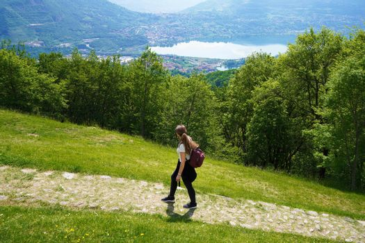 Female hiker walks the trail and looks with satisfaction from the top of mountain the lake
