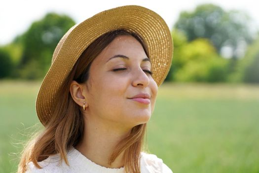 Close up of girl breathing deep fresh air with closed eyes