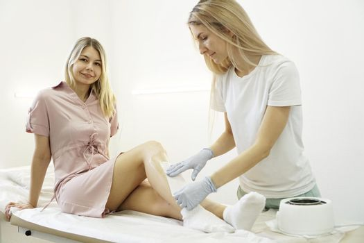 Hair removal from beautiful female legs. Waxing in a beauty salon