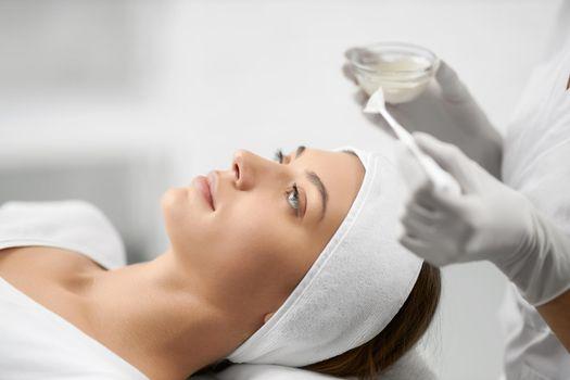 Beautiful woman doing procedure for face in beautician.