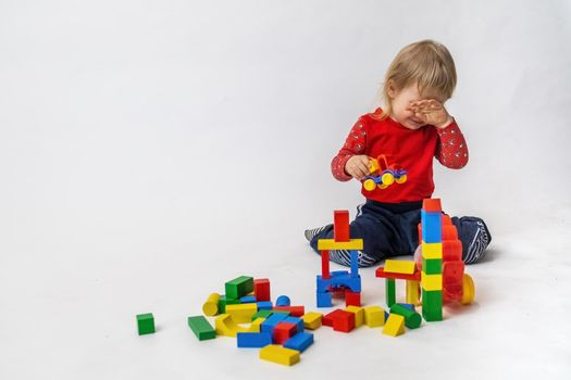 Crying little boy is playing with colorful wooden cubes