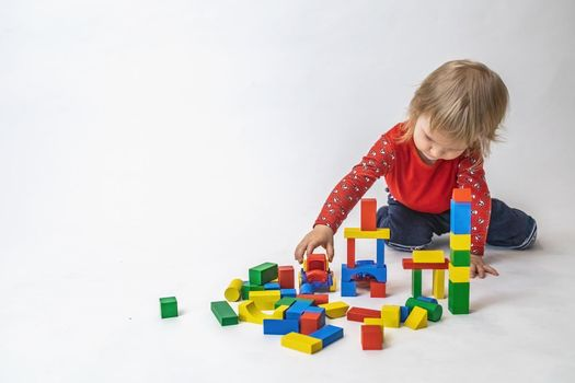 Little boy is playing with cubes