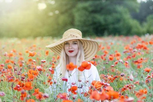 Attractive young woman posing in red poppy field.