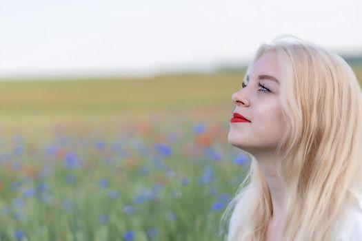 Side view of sunbathing beautiful young woman posing in summer field