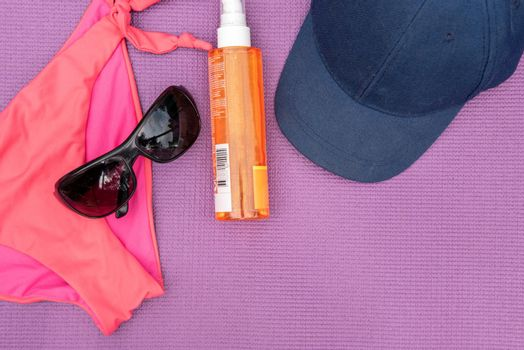Top view of summer accessories on purple background