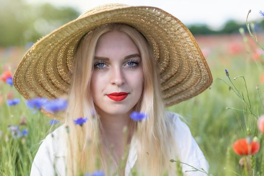 Front view portrait of beautiful  young woman in straw hat iposing  outdoors