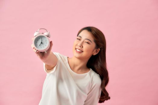 Beautiful young woman with white alarm clock on pink background