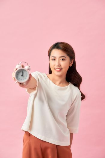 Happy young woman holding white alarm clock and waving hand isolated on pink