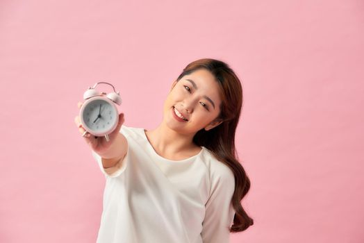 Young Asian woman with a clock on pink background