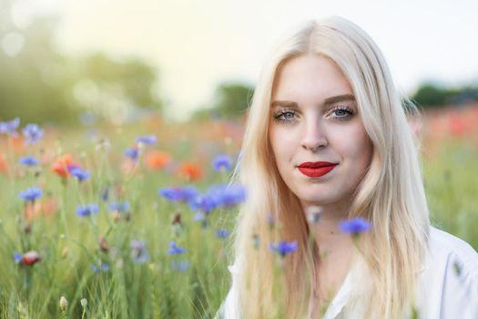 Portrait of attractive blonde woman posing in summer meadow