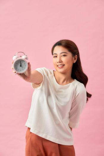 Cute laughing positive girl holding an alarm clock.