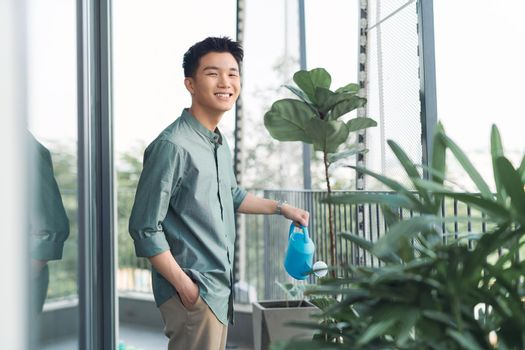 Man watering plant in container on balcony garden