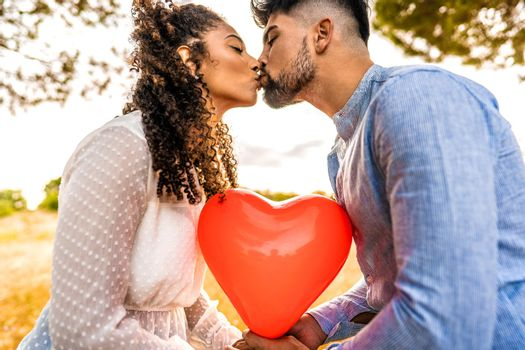 Profile photograph of multiracial couple in love kissing at sunset in nature with sun backlit effect on red heart shaped balloon among them. Romantic scene at dusk of two heterosexual young people