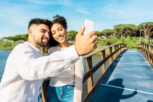 Happy multiracial couple in love staying on a wooden bridge taking a selfie in nature vacations. Handsome guy photographing himself with Hispanic girlfriend using smartphone. New technology habits