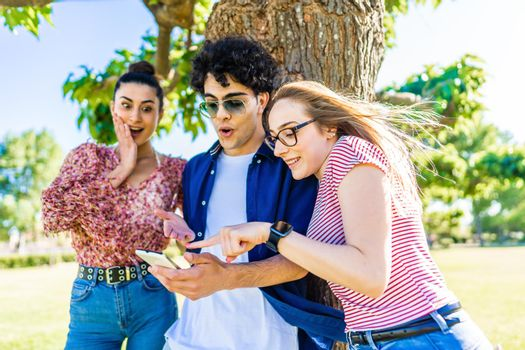 Three young friends in city park with surprised faces pointing smartphone enjoying social networks on mobile cell. Young people having fun together in nature with wi-fi internet connection technology