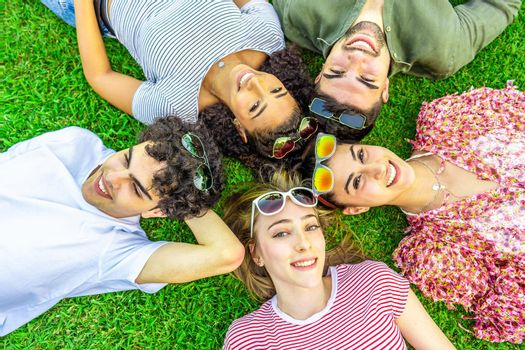 Shot from above of five happy multiracial friends lying head to head with colored sunglasses looking at camera from bottom. Mixed race group of smiling cute young people having fun together in nature