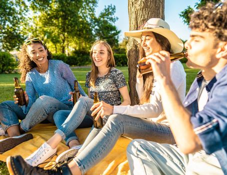 Happy friend group outdoor in city park drinking beer from bottle celebrating sitting on grass. Carefree young smiling people having fun in nature with alcohol at sunset enjoying a picnic in the grass